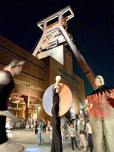 ExtraSchicht 2019: Walking Acts unter dem Förderturm der Zeche Zollverein.