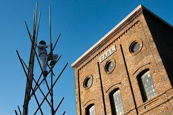 Ein Turm aus langen Holzstäben entsteht vor dem alten Malakowturm der Zeche Carl in Essen.