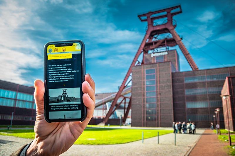 Eine Hand hält ein Smartphone mit der App Perspektivwechsel vor der Zeche Zollverein in die Höhe.