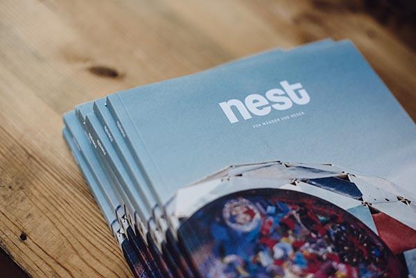 Ein Stapel der ersten Ausgabe vom NEST Magazin auf einem Holztisch.